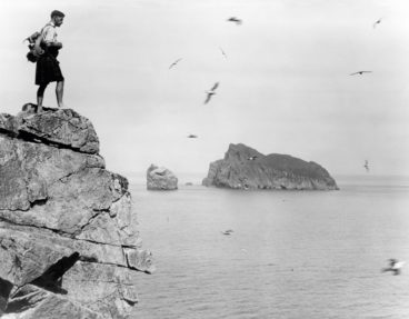 A man standing on a cliff edge on Hirta, St Kilda.